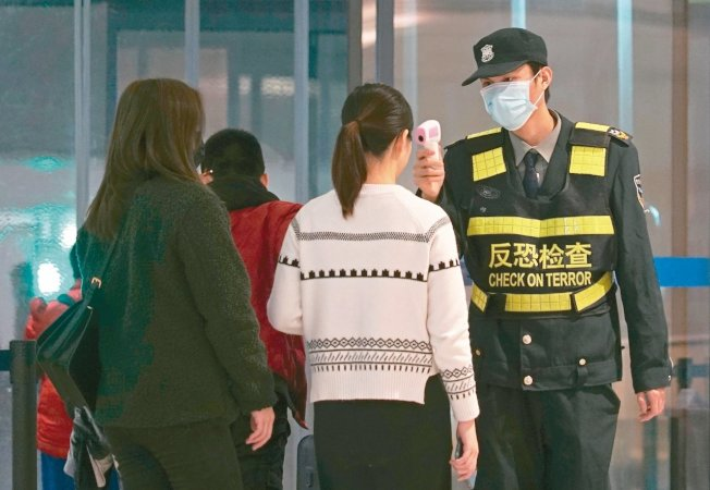 武漢肺炎疫情延燒,武漢天河機場工作人員為旅客量體溫。(美聯社)
