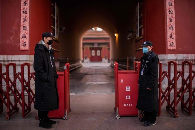 中共中央總書記習近平坦承新型冠狀病毒疫情加快蔓延,形勢嚴重,圖為北京故宮工作人員戴著口罩嚴控人員出入。(Getty Images)