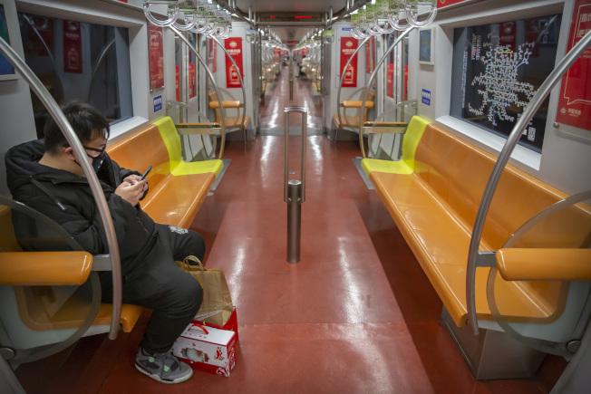 26日的北京地鐵幾乎無人搭乘,車廂內只有零星幾位乘客,戴著口罩。(美聯社)