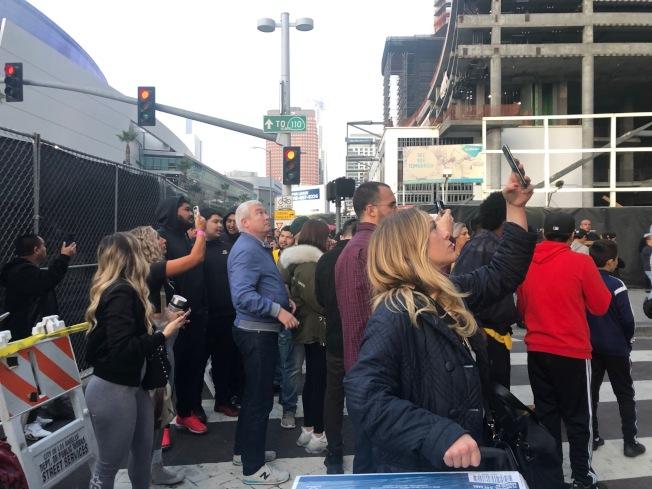 人們在Staples Center前拍攝大屏幕上的柯比。(記者張宏/攝影)