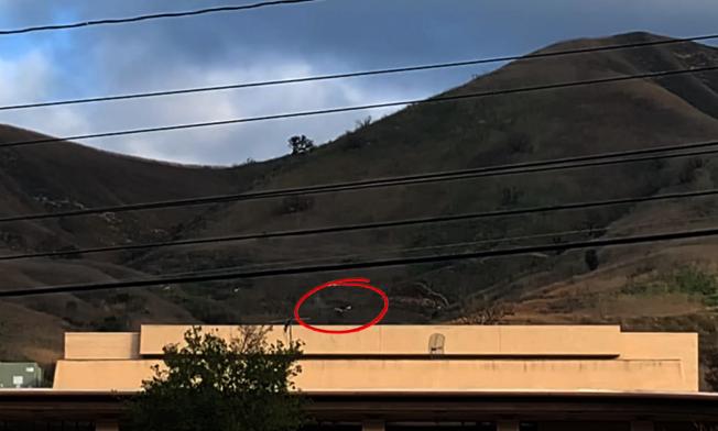 26日下午3時,山坡上仍可見直升機殘骸(紅圈處)。(記者陳開/攝影)