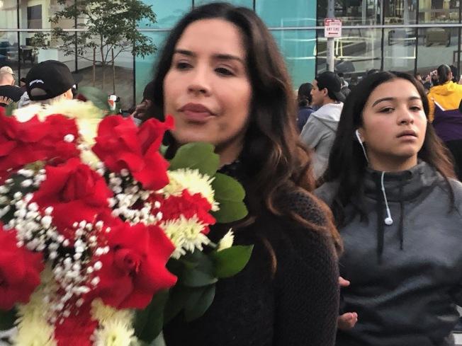 人們拿著送別的鮮花悼念遽逝的職籃巨星柯比。(記者張宏/攝影)