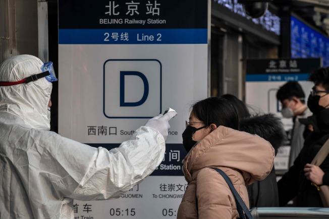 圖為一名穿著防護衣服在北京地鐵站入口處檢查體溫。Getty Images