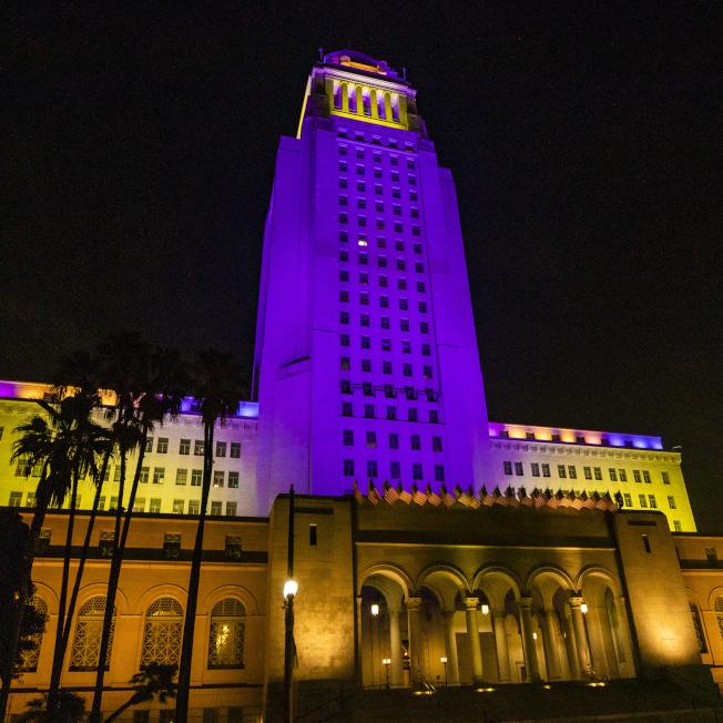 美國職籃NBA退役球星柯比‧布萊恩特墜機早逝,悲傷籠罩洛杉磯,市政廳打上紫金燈光紀念。(取自推特)