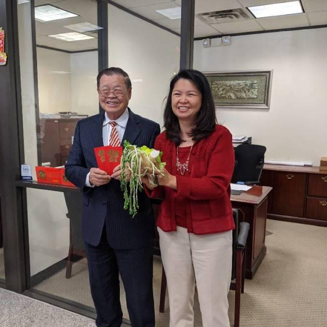 美南銀行前任董事長李昭寬(左)與李承穗(右)拿起舞獅踩碎的菜頭。(記者蕭永群/攝影)