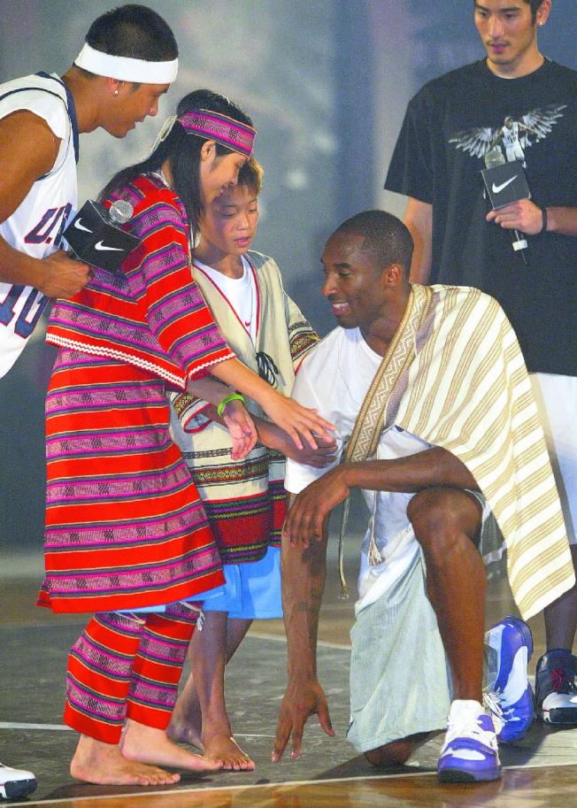 2007年9月,新竹五峰鄉桃山國小學童為布萊恩特(蹲者)披上泰雅族勇士的披肩與彩帶,感謝他協助整建體育館。(本報資料照片)