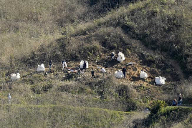 洛杉磯當局28日在洛杉磯湖人隊傳奇球星柯比‧布萊恩特墜機現場,尋獲九具罹難者屍體,但仍待辨識個別身分。(美聯社)