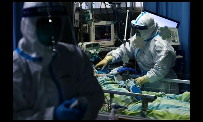 中國武漢肺炎確診病例已逼近6000例。圖為武漢大學中南醫院重症隔離病房,醫護人員正在為病人治療。(新華社)