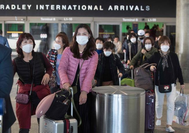 由亞洲飛抵洛杉磯的航班,29日下機旅客大多戴著口罩入境。(Getty Images)