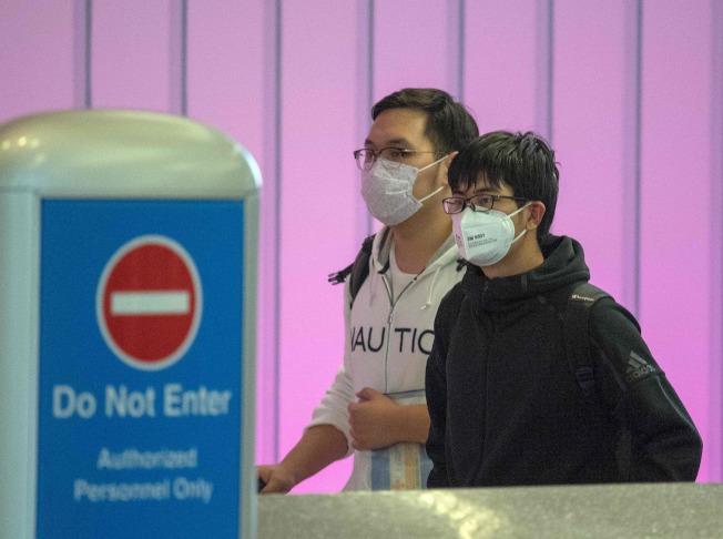 由亞洲飛抵洛杉磯的旅客,29日戴著口罩在洛杉磯機場入境。(Getty Images)