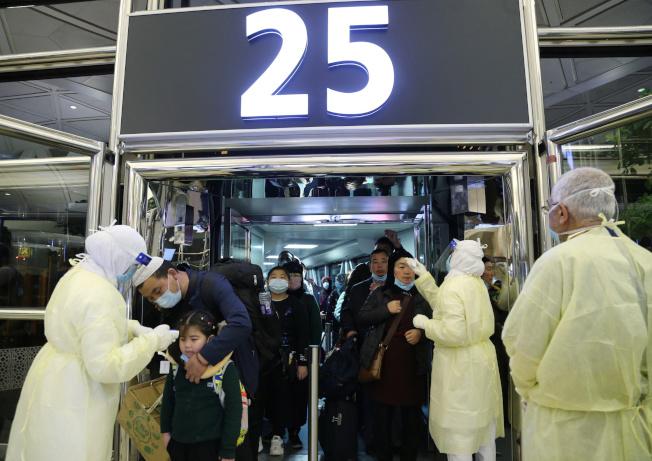 中東也出現武漢肺炎確診病例,引起各國恐慌,圖為沙烏地阿拉伯衛生官員在機場為入境旅客測量體溫。(路透)