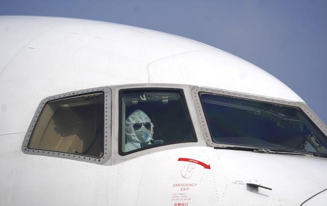湖北武漢是新型冠狀病毒肺炎的重災區,圖為一名貨機駕駛員穿著全副防護服抵達武漢天河機場。(美聯社)