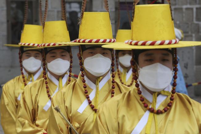 南韓首爾德壽宮前,皇家守衛隊在換崗儀式時守衛戴上口罩。(美聯社)