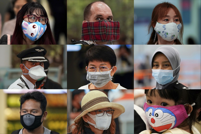 29日這天,在馬來西亞吉隆坡機場來來往往人群中,攝影師拍下了旅客眾生相。他們的共同點——戴了口罩。(美聯社)