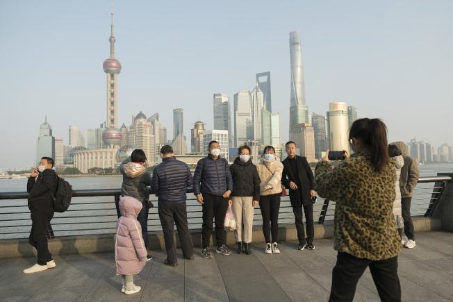 30日,在中國上海,旅客在跟地標合影時不忘戴上口罩。(美聯社)