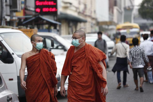 緬甸仰光街頭,兩位僧人也戴上了口罩。(Getty Images)