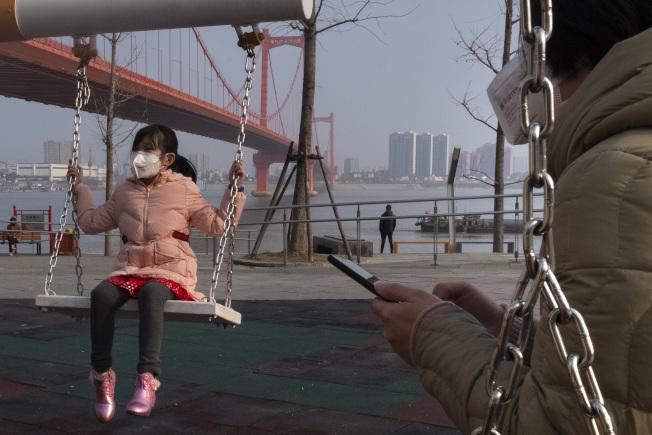 在新型冠狀病毒爆發地、重災區武漢,鸚鵡洲長江大橋邊上,一個小女孩戴著口罩蕩鞦韆。(美聯社)