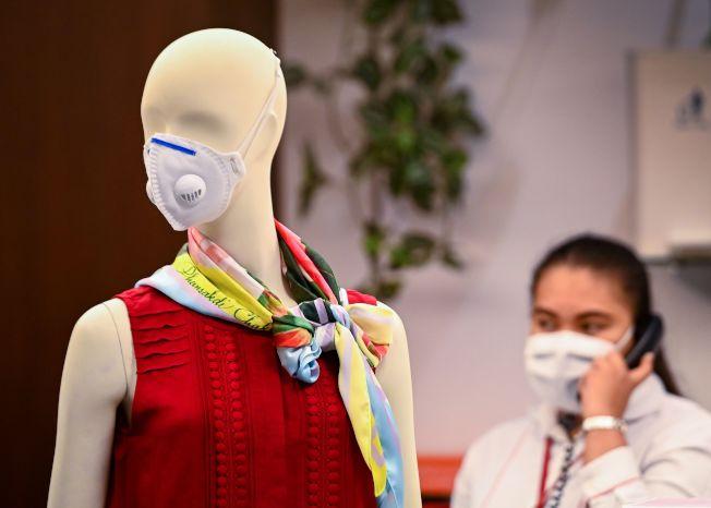 泰國曼谷一家購物中心,一個女店員戴著口罩打電話。(Getty Images)
