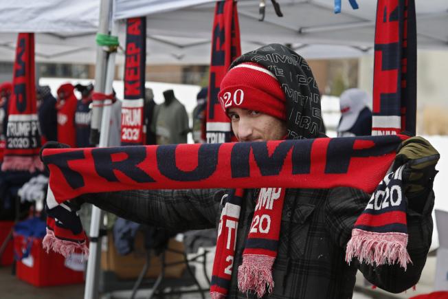 川普總統在參院彈劾審理即將針對是否傳喚新證人投票前夕,前往美中地區造勢。圖為一名支持者在愛阿華州活動現場展示川普圍巾。(美聯社)
