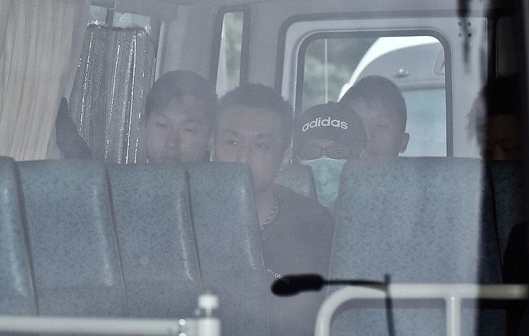 季炳雄(戴黑帽口罩者)18日早上出獄,他在多輛警車押解下,直赴機場遞解到美國。(中央社)