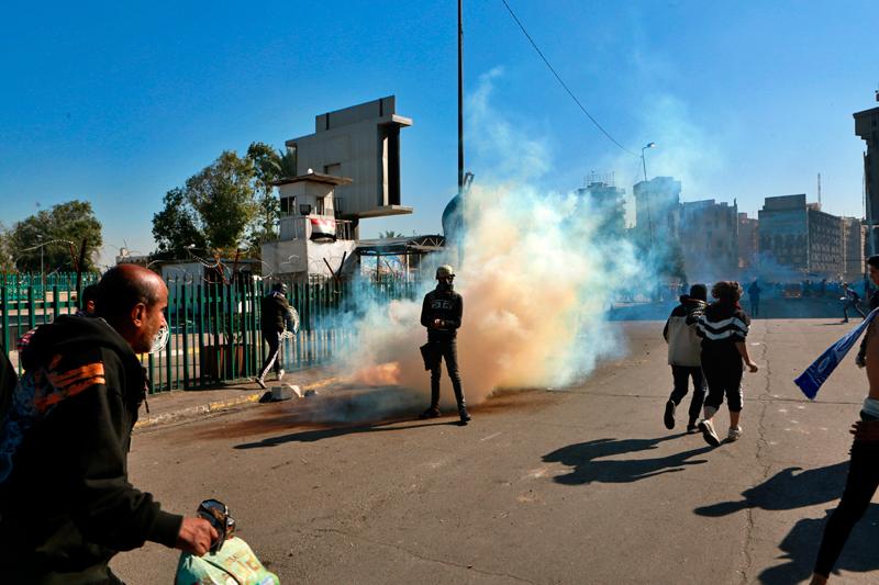 圖為27日安全部隊在與巴格達的反政府示威者發生衝突時,發射催淚瓦斯。美聯社