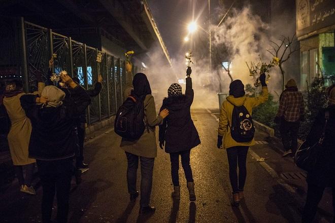 伊朗人民13日在阿米爾卡比爾理工大學前手持花朵,與施放催淚瓦斯的抗暴警察對峙。(Getty Images)