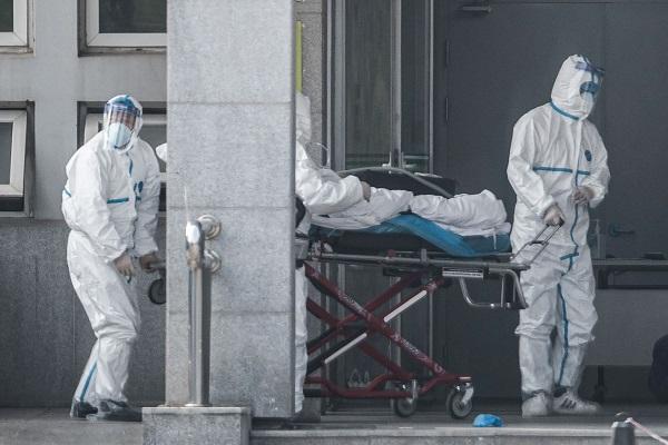 武漢肺炎患病數字持續攀升,圖為18日醫護人員將一名病人運進武漢金銀潭醫院。(Getty Images)