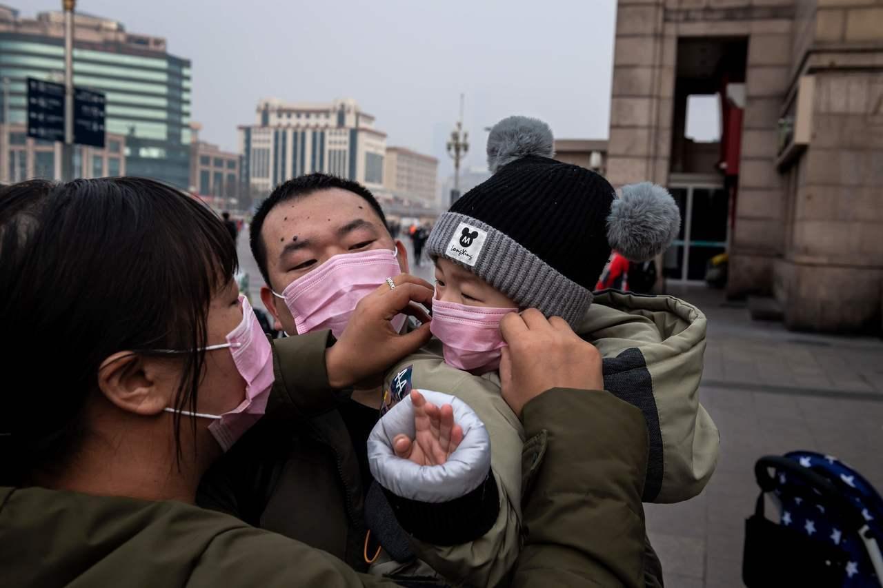 在北京車站,媽媽幫孩子把口罩戴好,以避免武漢肺炎傳染。(Getty Images)
