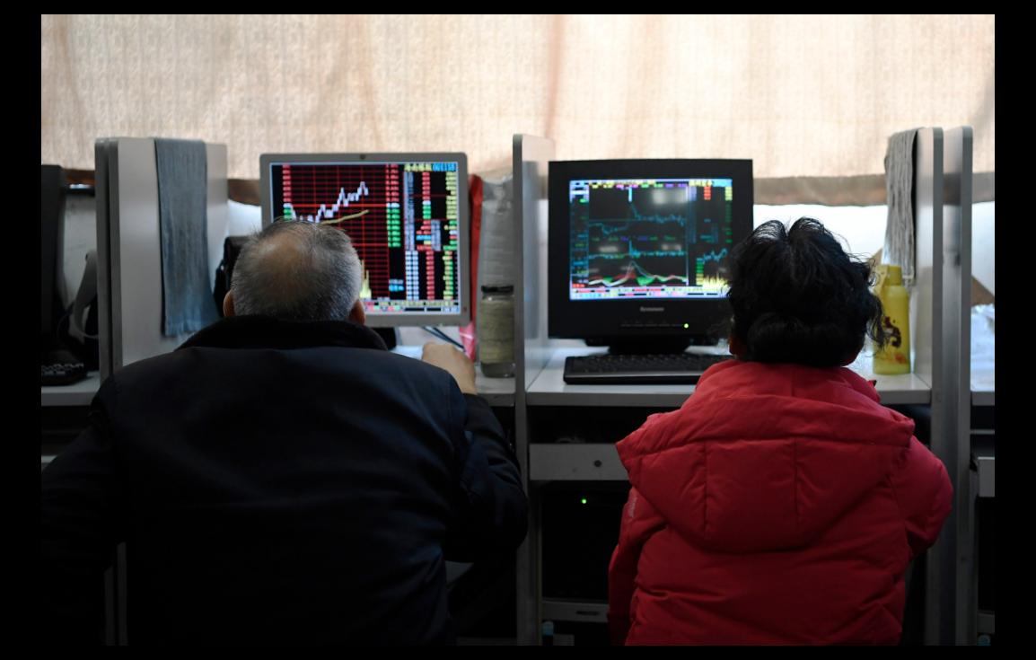 中國A股在春節前就已應對疫情恐慌情緒升溫,出現了放量大跌的走勢。圖為四川成都某券商營業廳內的投資人正透過電腦關注股市走勢。(中新社)