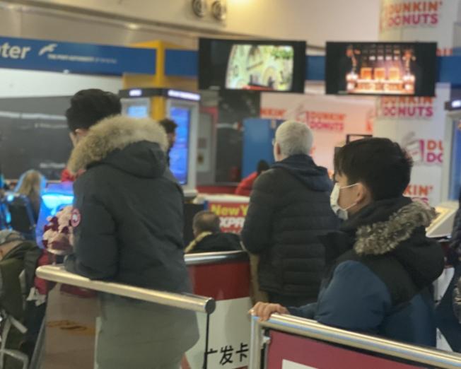 不少在JFK接機的華裔民眾已配戴口罩。(記者牟蘭/攝影)