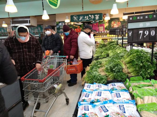 黃岡市區範圍內1日起實行居民出行管控措施,每戶家庭每兩天可指派一名家庭成員上街採購生活物資。圖為湖北市民戴着口罩在超市購物。(路透)