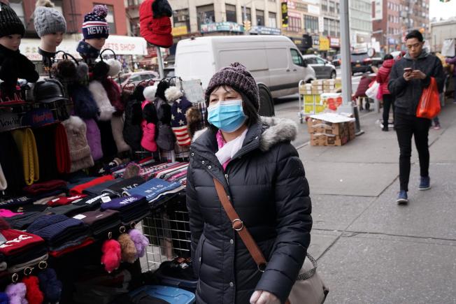 新型冠狀肺炎病毒肺炎在中國爆發,全球華埠都受衝擊,圖為紐約曼哈頓華埠的行人戴著口罩。(路透)
