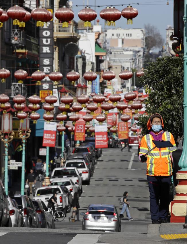 新型冠狀肺炎病毒肺炎在中國爆發,全球華埠都受衝擊,圖為舊金山華埠較平常冷清,清潔工人戴著口罩掃街。(美聯社)