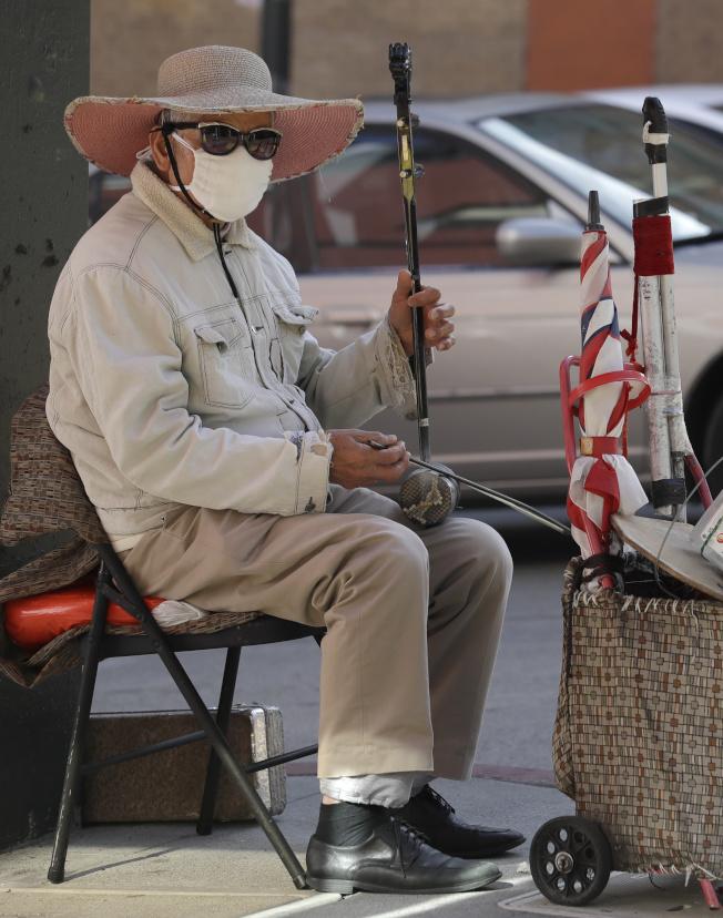 新型冠狀病毒疫情擴大,各地華埠都提高警覺。圖為舊金山華埠街頭藝術家戴著口罩獻藝。(美聯社)