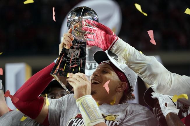 第54屆NFL職業美式足球超級盃2日在邁阿密舉行,堪薩斯市酋長隊上演逆轉好戲,以31:20力克舊金山四九人隊,獲得冠軍。圖為酋長隊四分衛馬霍姆斯手持超級盃與隊員開心共舞。(美聯社)