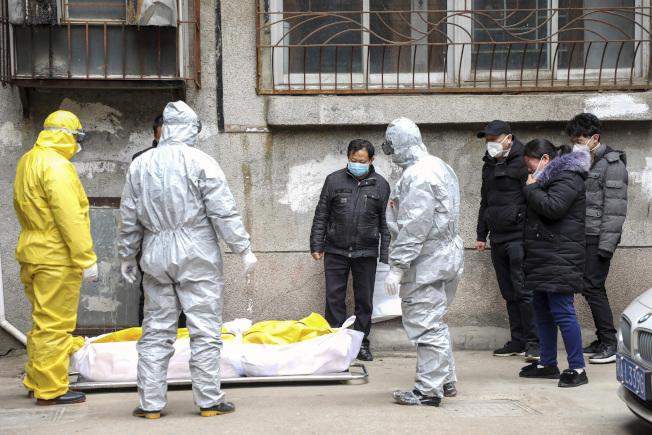 全副防護服的武漢殯儀館工作人員2日從住宅內抬走一位疑似死於武漢肺炎的屍體。(美聯社)