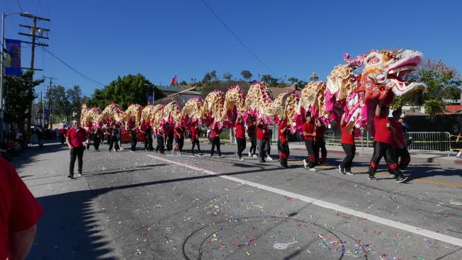 舞龍和舞獅隊不斷和路邊民眾互動。(記者李雪╱攝影)