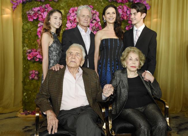 硬漢男星寇克道格拉斯(前左)5日以103歲高齡辭世。圖為他2016年12月9日百歲生日時,握著妻子的手,和麥可道格拉斯(後左二)一家合影。(美聯社)