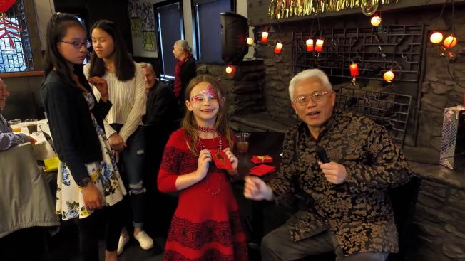僑務促進委員吳天順(右)發紅包給小朋友。(孫博先提供)
