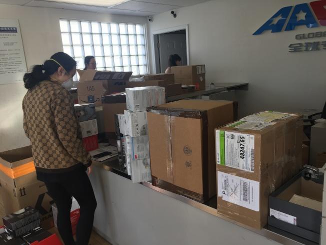 蒙市一家快遞公司工作人員正在忙著收件,負責人告知顧客價格不變,但無法按時送達。(記者啟鉻/攝影)