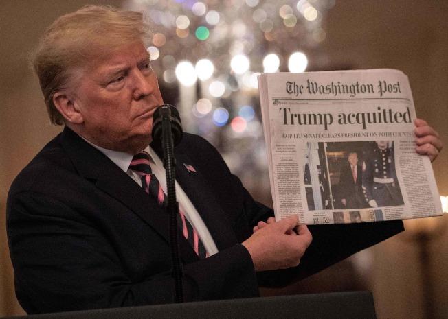 川普總統手持華盛頓郵報,頭版大標題寫著「川普無罪」。(美聯社)