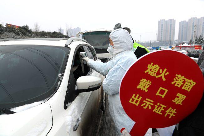中國企業開工在即,各地方政府都嚴陣以待,加強防疫措施。河南鄭州的重要交通卡口設立防疫服務站,「逢車必檢、逢人必查」。(中新社)