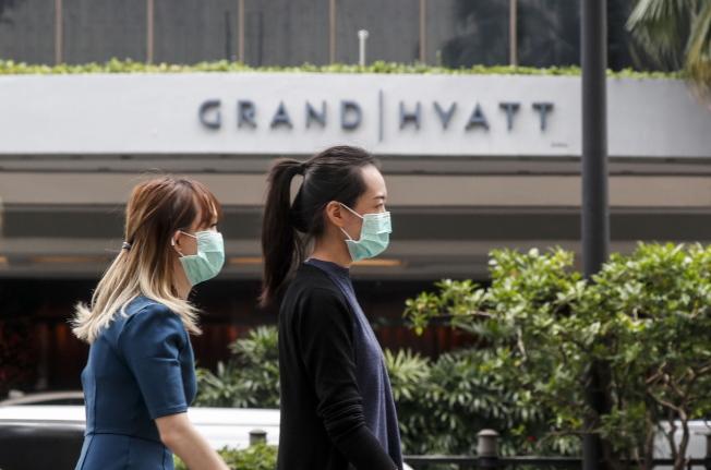 英國氣體分析儀器公司仕富梅1月在新加坡君悅酒店舉行會議,100多名與會者中3人返國後感染新冠肺炎。兩名婦女7日戴口罩走過新加坡君悅酒店。(歐新社)