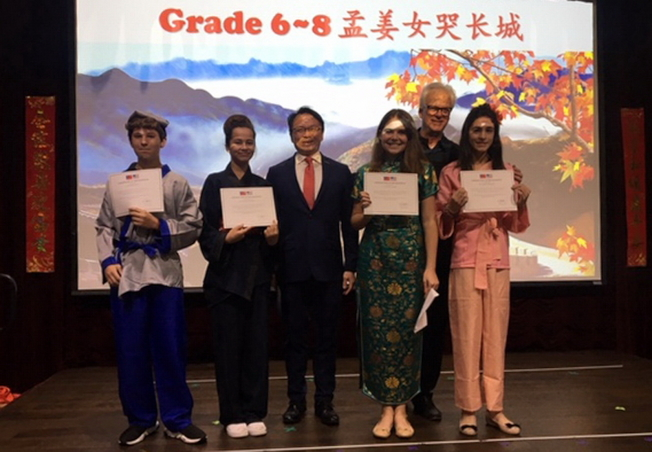 駐邁經文處處長錢冠州(左三)頒發獎狀給參與陽光島灘市與台灣恆春姊妹市慶祝活動表演的學生。(孫博先提供)