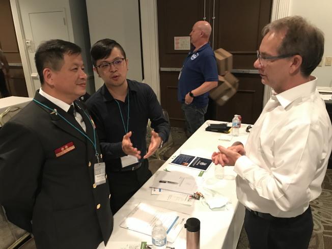 新北市政府消防局副局長陳崇岳(左一)於消防指揮科技年會中與荷蘭VR軟件的美國代表交流,右為ADMS總裁Marco van Wijngaarden。(鄭鴻鈞提供)