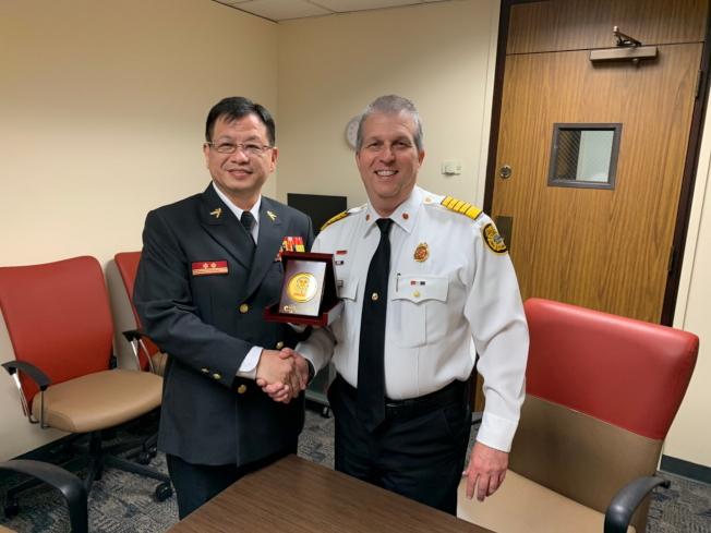 新北市政府消防局副局長陳崇岳(左)與坦帕市消防局長Nick LoCicero相談甚歡。(鄭鴻鈞提供)