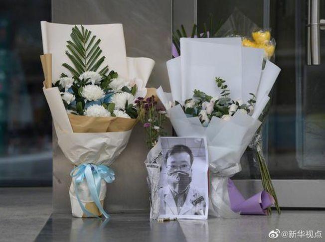 2月7日,在李文亮生前工作過的武漢中心醫院後湖院區門診樓門口,擺放著他的黑白打印照片和祭奠鮮花。(取材自環球網)