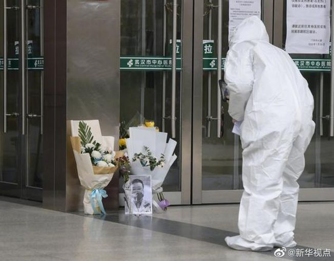 穿著防護衣的防疫人員悼念李文亮。(取材自環球網)