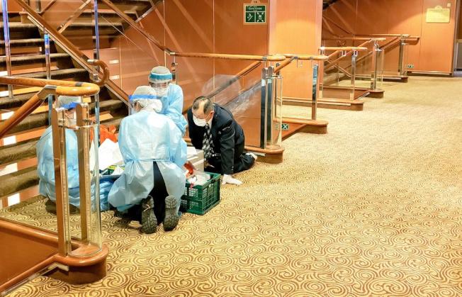 停靠日本橫濱港的郵輪「鑽石公主號」至少有64名乘客感染新冠肺炎。圖為穿上全套防護服的衛生官員為乘客檢疫。(路透)