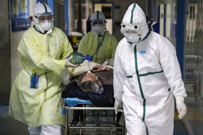 新冠肺炎的死亡病例已經超過SARS,圖為武漢醫護人員搶救病患。(美聯社)